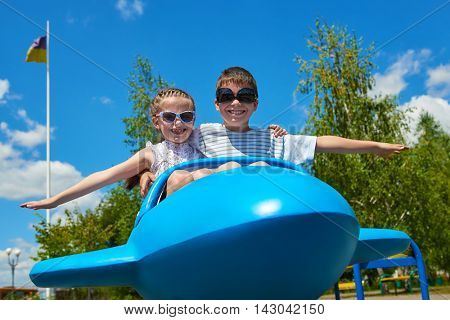 two child fly on blue airplane attraction in park, happy childhood, summer vacation concept