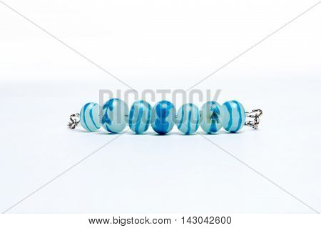 Bracelet with blue glass beads on white background