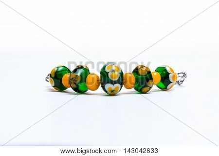 Bracelet with green and orange glass beads on white background