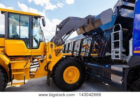Image of a yellow backhoe using a scoop to load soil into truck, isolated on white background