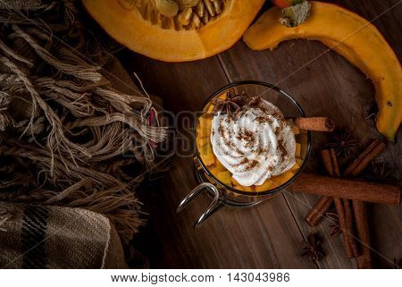Concept: fragrant autumn drink - all you need for pumpkin coffee latte with whipped cream and spices - aniseed and cinnamon. On the wooden background, next to a warm blanket, spices and pumpkin.