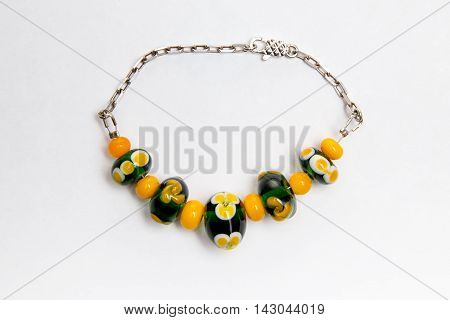 Bijouterie with green and orange beads on white background