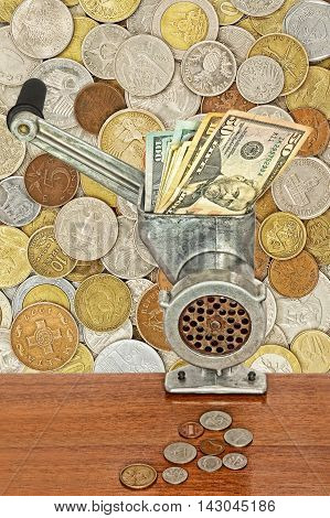 Money and business concept.Dollar banknotes in meat grinder and coins on table on lot of different coins background.