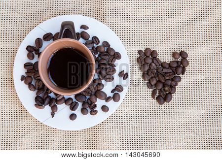 Cup of aromatic espresso black coffee and roasted beans creating the symbol of love. I love coffee concept