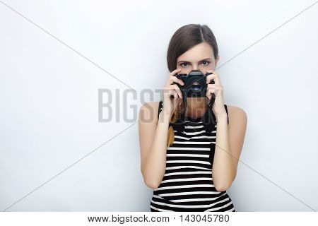 Portrait Of Happy Young Beautiful Woman In Striped Shirt Posing With Black Photo Camera Hiding Her F