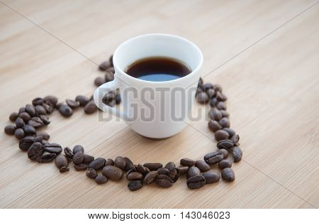 Coffee beans in the shape of heart symbol and a cup of black espresso coffee. Concept of I love coffee.