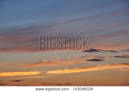 Cumulus and cirrus clouds sundown. Clouds of golden and orange. Background