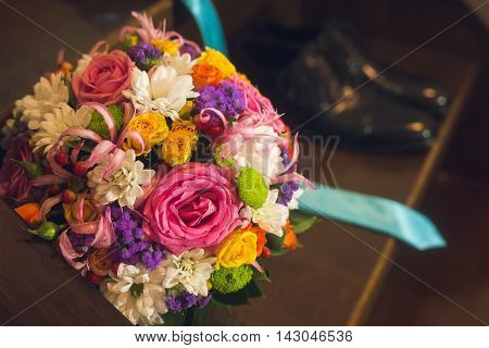 Beautiful composition with a flower bouquet and wedding groom shoes