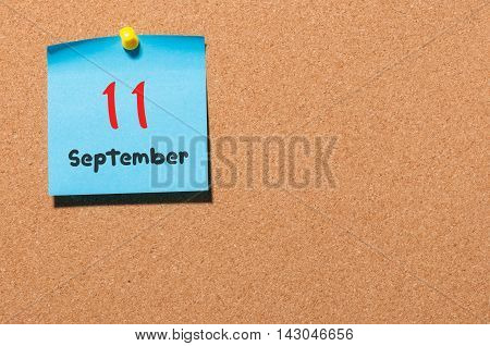 September 11th. Day 11 of month, color sticker calendar on notice board. Autumn time. Empty space for text.