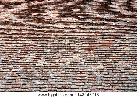 Symmetric textured brown background from church roof clay tiles