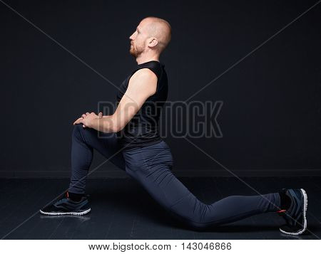Young fitness man performing stretching of the thigh quadriceps doing forward lunge