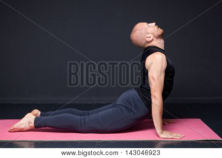 Young yogi man performing cobra pose on the mat
