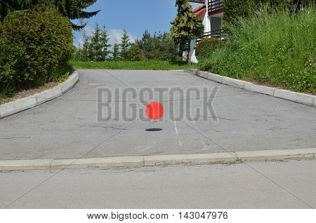 Blank red round metal plate hanging on a stretched wire to stop entry to a private property. Suitable for text