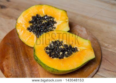 Ripe papaya .Sliced fresh papaya on wooden background.