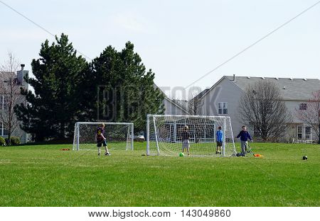 JOLIET, ILLINOIS / UNITED STATES - MARCH 26, 2016: Children play a game of soccer on a neighborhood soccer field in the Joliet's Wesmere Country Club subdivision.