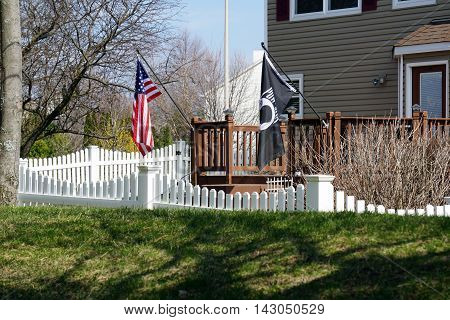 JOLIET, ILLINOIS / UNITED STATES - MARCH 26, 2016: The American flag and the POW-MIA flag are displayed from the deck railing behind a home in Joliet's Wesmere Country Club subdivision.