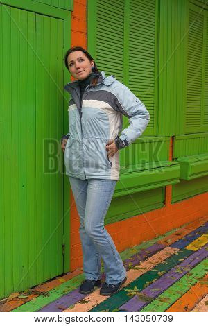 Woman in a jacket standing at the colorful walls. People