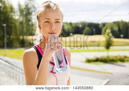 Fit and beautiful blonde woman in sportswear taking a break after workout or running. Stands at the countryside in pink and white top.
