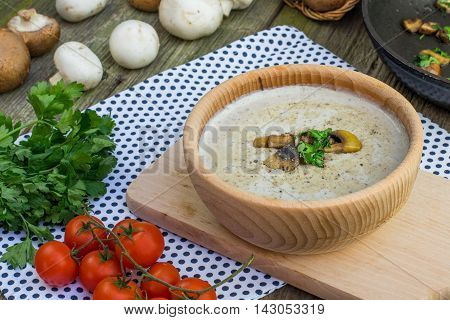 Creamy Champignon Soup In Wooden Bowl With Sautéed Champignon Mushrooms With Tomatoes