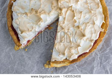 Top View On Sliced Meringue Cake With Strawberry Jam On Baking Paper