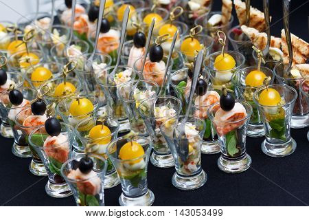Mini Canape with meat and vegetables in glass cups, stand on the black table.
