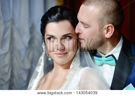 Wedding Couple Indoors Is Hugging Each Other. Beautiful Model Girl In White Dress. Man In Suit. Beau
