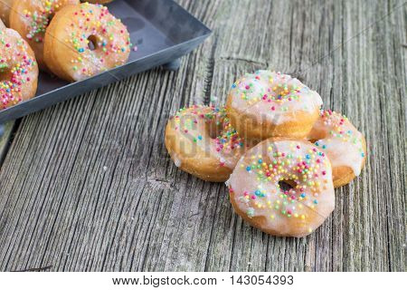 White Sugar Glazed Mini Donuts On Old Wooden Board