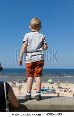 The Boy Looks From The Embankment At The Sea