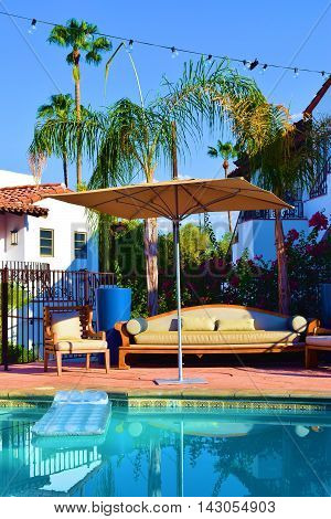 Floating raft in a pool surrounded with outdoor furniture and Palm Trees taken in a courtyard garden