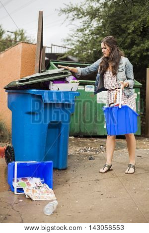 Young woman wonders where to dump personal recycle bin.