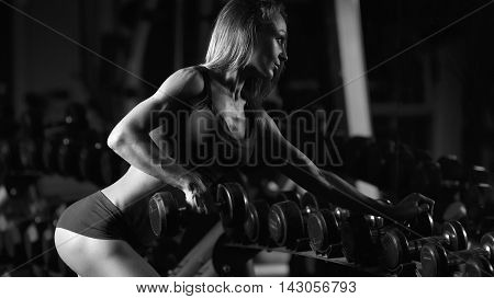 Black and white photo fitness woman in the gym. Muscular blonde fitness woman doing exercises in the gym