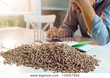 Man calculating household heating costs. Wooden pellets biomass effective environmentally friendly and economical heating sustainable and renewable energy