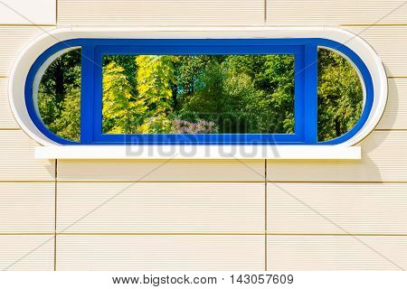 Bright green foliage reflection into futuristic modern style elliptic window. Ecologic residential concept