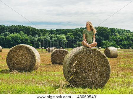 Young blond girl with long hair sitting legs crossed on haystack and smiling with closed eyes on sunny summer day, Badasconytomaj, Hungary