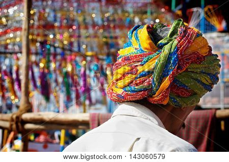 Man wearing a turban in a marketplace in India.