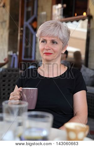 Woman In Cafe Drinking Coffee