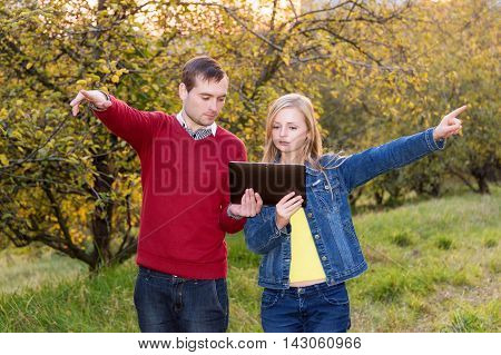 Young couple man and woman pointing in opposite directions holding map on the tablet and planning trip or get lost in the woods