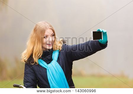 Happy woman in fall autumn park taking selfie self photo picture. Glad young girl in jacket and scarf relaxing.