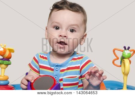 Cute baby boy sitting and playing with toys.  Adorable six month old child happy smiling.