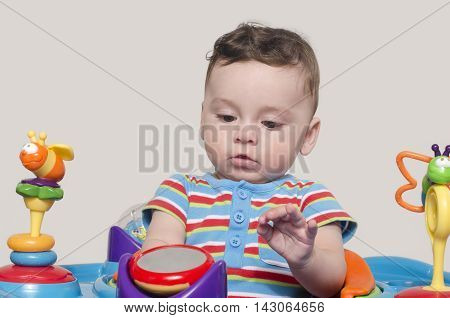 Cute baby boy sitting and playing with toys.  Adorable six month old child looking at his toys.