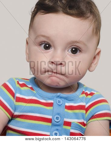 Portrait of an adorable six month old child looking away thinking. Cute baby boy sitting and wondering.