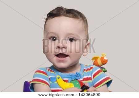 Cute baby boy sitting and playing with toys. Adorable six month old child happy laughing.