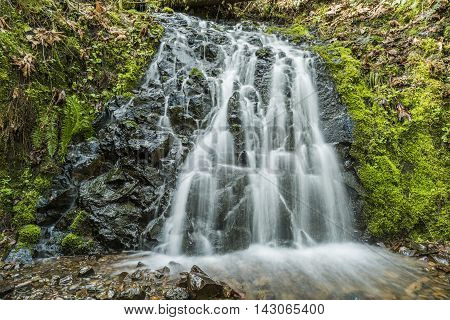 Small wide bridal veil waterfall with mossy rocks and smooth flowing water in Oregon