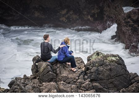Cape Perpetua, USA - February 27, 2016: Two hikers giving massage on ocean cliff during cold weather