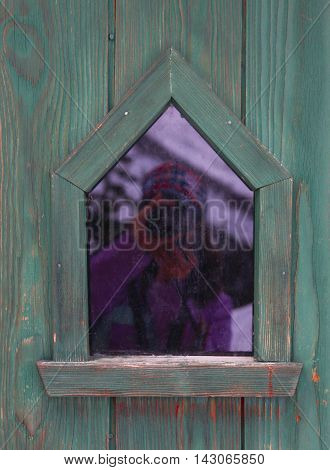Small window in green wooden wall with reflection of photographer