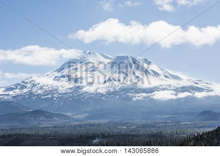 Snowcapped Mount Shasta volcano during winter with valley view and clouds on mountain