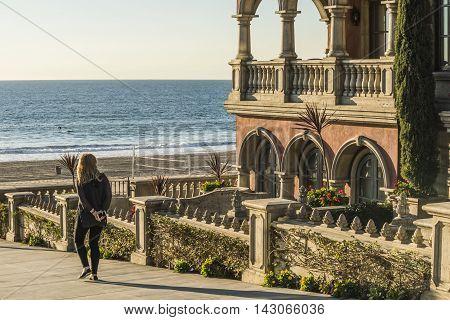 Manhattan Beach, USA - December 17, 2015: Blonde woman walking to beach boardwalk in Los Angeles area by Italian style house