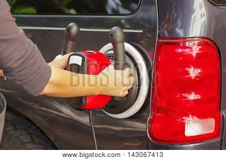 man with a power buffer machine cleaning the back part of a car.
