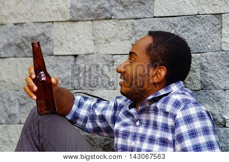 Man wearing casual clothes sitting drunk holding brown beer bottle next to grey brick wall, drunken smile.