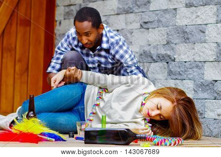 Woman wearing casual clothes lying drunk passed out on wooden surface, man sitting beside her trying to get contact by touching and grabbing womans arm.